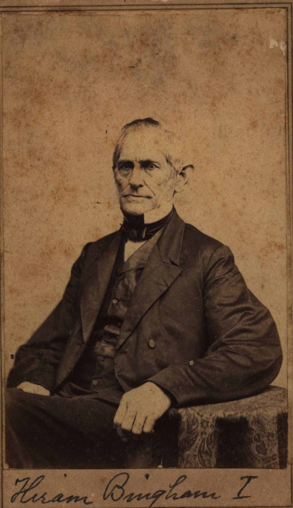 """A black and white photograph on worn and weathered paper of a seated man in a three-piece black suit and bowtie. His hair is graying and combed over to one side. His left arm rests on a table with a paisley-patterned cloth draped over it. The bottom of the photo is hand-captioned, """"Hiram Bingham I."""""""