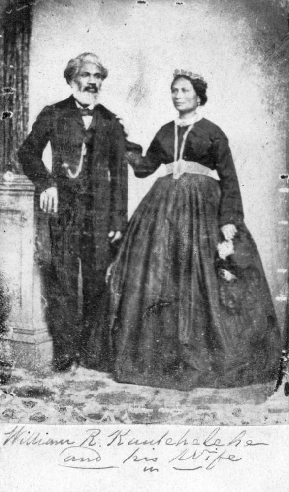 """A black and white photograph on aged and worn paper. A man and woman in dress clothes stand side by side. The man is resting his arm on a pillar and the woman is reaching her right arm up to rest on his shoulder. The man is bearded and wearing a three-piece black suit and bowtie, and a chain hangs from his chest down into his pocket. The woman is wearing a large black dress with light-colored belt and collar accents. She is wearing a crown and long necklace. The bottom of the photo is hand-captioned, """"William Kaulehelehe and his Wife."""""""