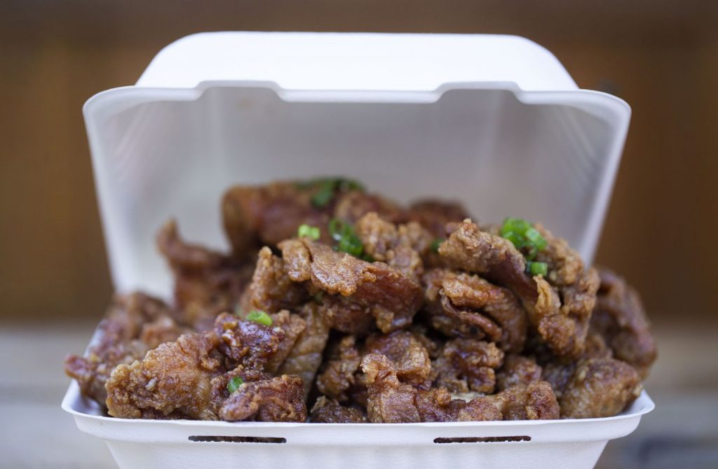 A close-up modern photograph of a chicken dish in white styrofoam take-out container. The chicken is golden-brown and garnished with green onions.