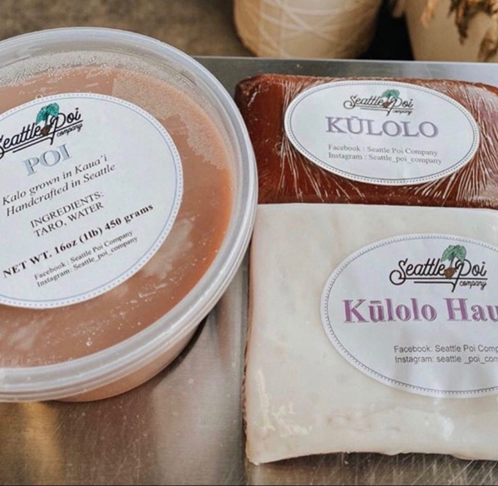 "A close-up modern color photograph of multiple food items packaged by Seattle Poi Company. There is a round 16 oz. plastic container labeled, ""POI, Kalo grown in Kaua'i, Handcrafted in Seattle, INGREDIENTS: TARO, WATER."" In plastic wrap, there is an item labeled, ""KŪLOLO"" and a second plastic wrapped item that's label is cut off by the edge of the photograph: ""KŪLOLO HAU..."""
