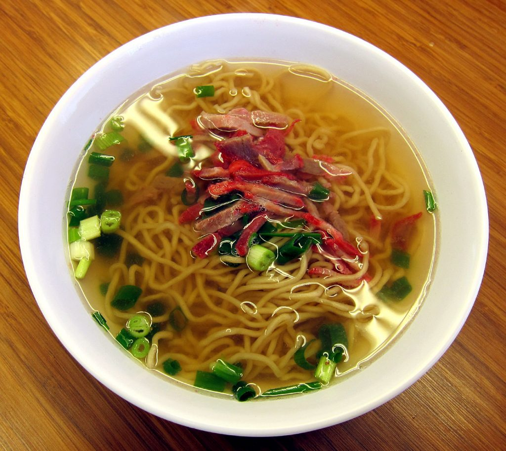 An up-close, modern color photograph of a bowl of noodle soup in a white bowl on a wood table. The broth and noodles are yellow, and the soup is garnished with chopped green onions and small slices of red meat.