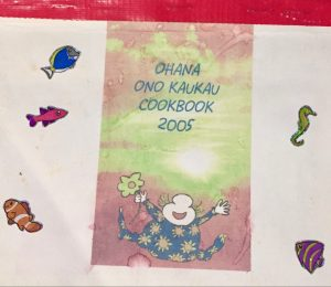 "Left: The cover of an aged handmade cookbook bound with red duct tape across the top. There is a green and red rectangle in the middle on an otherwise white cover. Inside the rectangle there is blue text that reads: ""OHANA ONO KAUKAU COOKBOOK 2005."" Below the text there is a cartoon figure jumping with a joyous expression on their face. The character's leg and arms are spread horizontally, they are wearing a blue outfit that has a yellow sun pattern all over it. They are holding a large yellow flower in their right hand. There are five shiny fish and brightly colored tropical fish stickers placed on the cover on either side of the rectangle."
