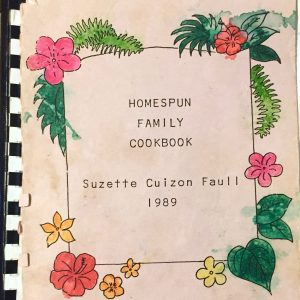 "Right: The cover of an aged, handmade cookbook bound with a black plastic binding comb, with the text: ""HOMESPUN FAMILY COOKBOOK."" Beneath the title the author's name is printed, ""Suzette Cuizon Faull,"" and beneath that, the year, 1989. Around the text there is a thin black line in a rectangle-like shape, eight flowers of various colors shapes and sizes, and other green foliage."