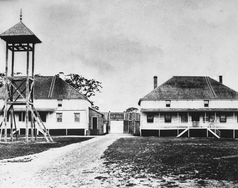 An aged black and white photograph of Fort Victoria. There are two primary buildings connected by a fence with an open gate that a road passes through. Each building has a ladder that reaches to the top of the roof. The building on the right has a porch that stretches across the length of the building and two chimney stacks on either side. In the foreground of the photograph there is a tall watchtower with a basic wood construction and small roof.