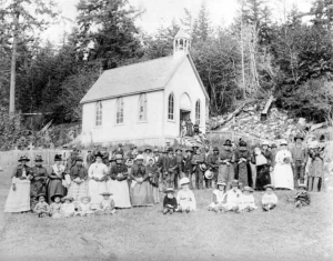 An aged black and white photograph of a large group of people gathered in front of a small, A-frame church built of wood that has a bell tower. The people are dressed in Anglo-attire and all of them are wearing a flat-brimmed hat. Twelve children sit on the ground in the front row. Women stand in a line behind the children, and men stand in a third line behind the women. There is a small cluster of people standing separately on the steps leading up to the church.