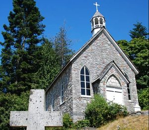 """A modern, color photograph of an A-frame church with a light grey and brown brick exterior and belltower. There is a small entryway built off the front of the basic A-frame structure. In the foreground there is a cross-shaped headstone that reads, """"RIP."""""""
