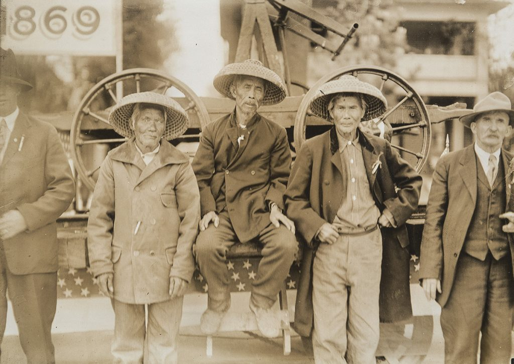 A sepia photograph of five male workers. All of them wear hats, and the three in the middle have a curved, woven brim. They are standing in front of a steel industrial machine.