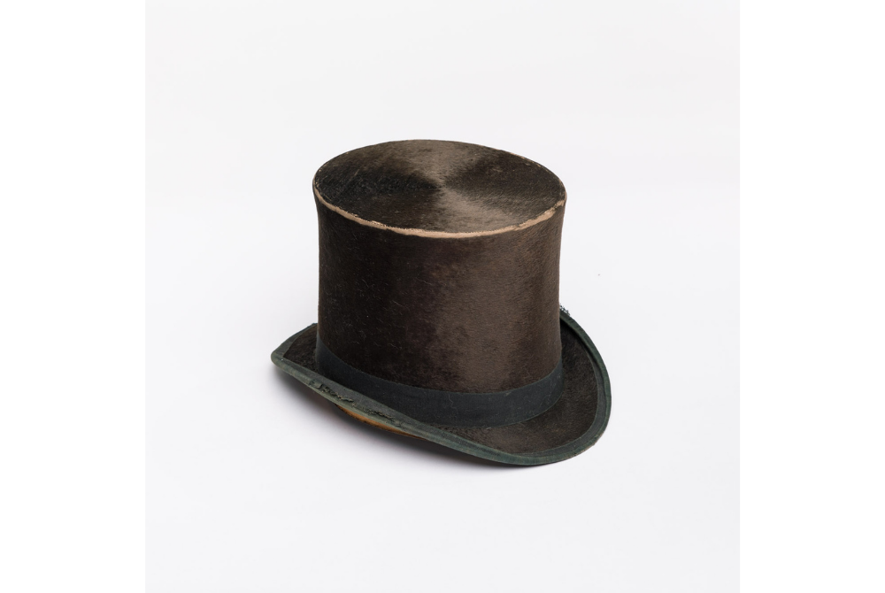 A photograph of a dark brown, well-worn beaver fur top hat against a plain white background. The rim around the top of the hat has lost fur and the bottom rim is fraying at the edges.