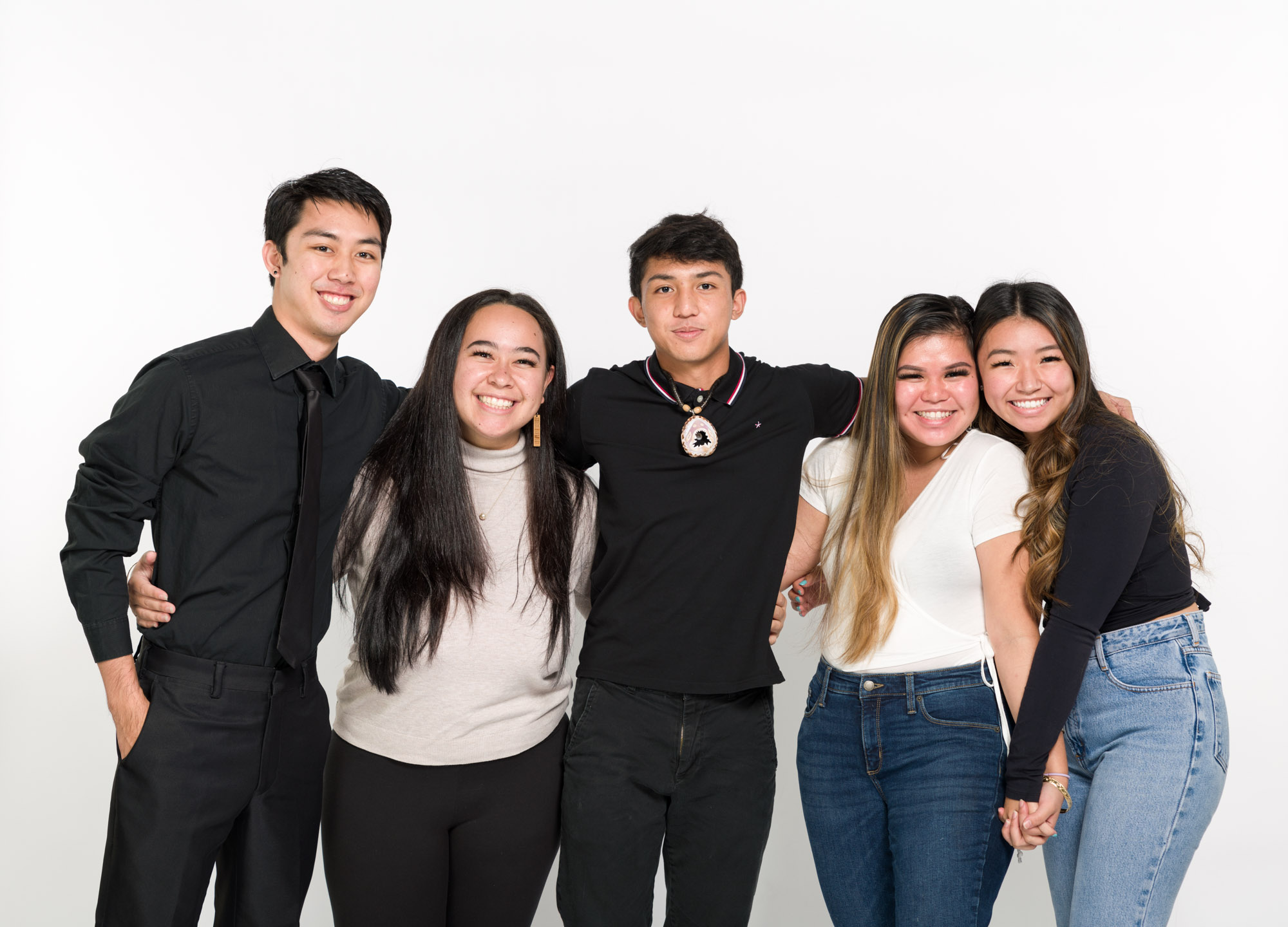 A modern color photograph of five young adults standing, posing to have their photo taken. Their arms are linked, and two hold hands.