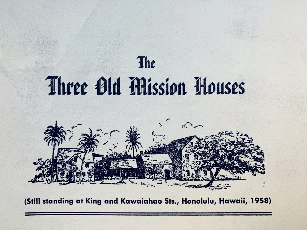 """A white tour guide pamphlet with a large black print title in an old gothic-type font that reads: """"The Three Old Mission Houses."""" Below the title there is a print of a cluster of four buildings among palm trees and other foliage. In smaller print below the image the pamphlet reads: """"(Still standing at King and Kawaiahao Sts., Honolulu, Hawaii, 1958)"""""""