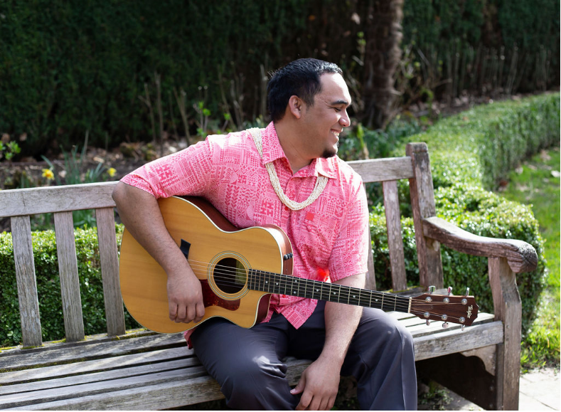 A modern, color photograph of a man sitting on a bench, holding an acoustic guitar, and smiling. He is wearing a bright pink patterned button-down shirt with a collar and a beaded necklace.