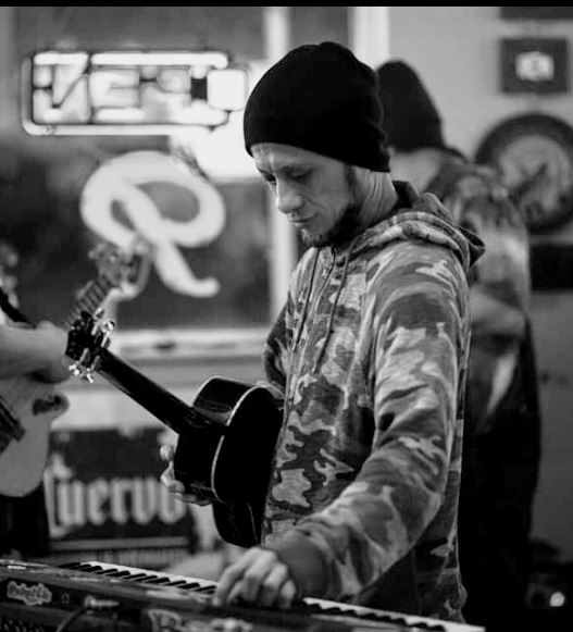 A modern, black and white photograph of a man holding an acoustic stringed instrument in one hand and playing an electric keyboard with the other. He is wearing a black beanie-style hat and camouflage print hoodie. In the background there are two other people, one of which is holding a string instrument.
