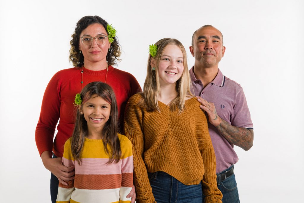 A modern, color photograph of a four-person family standing in front of a white backdrop. In the back row is a woman with curly brown hair, wearing glasses and a flower in her hair, and her hand is on her daughter's arm. Next to her is a man wearing a purple polo shirt. He has his hand on his daughter's shoulder. The two girls are smiling at the camera and have matching flowers in their hair.