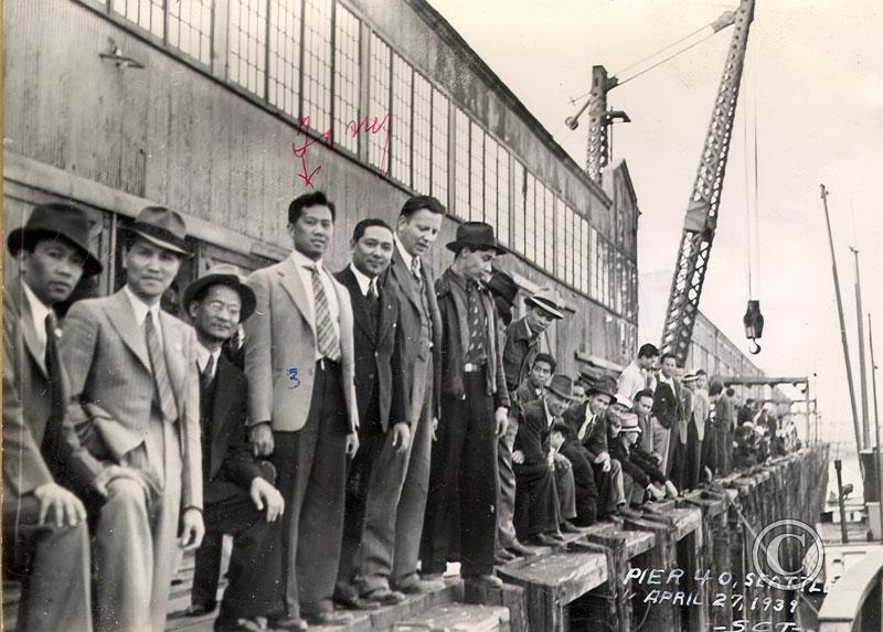 An aged, black and white photograph of a large group of male Filipino workers lined up along a dock. In the background there are port buildings and cranes.