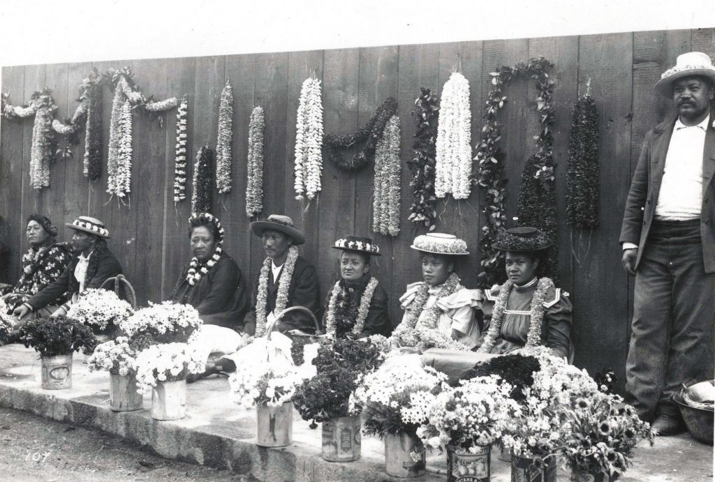 A black and white photograph of a row of eight people selling leis. All but the person furthest to the right are sitting on the ground, and all of them are wearing a hat and/or a lei on their head. Behind them, leis hang from wood paneling, and in front of them, there are about 12 bouquets of flowers of various kinds and sizes.