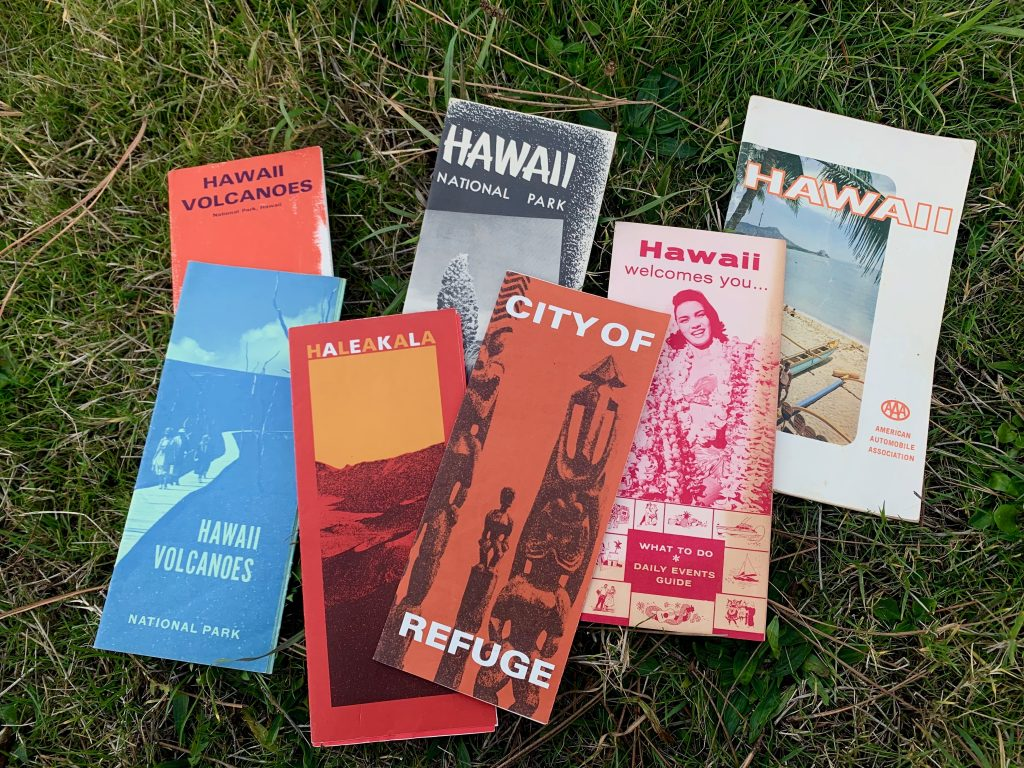 """A modern, color photograph of seven travel brochures on grass. From left to right, the brochures are titled: """"Hawaii Volcanoes,"""" """"Hawaii National Park,"""" """"Hawaii,"""" """"Hawaii Volcanoes National Park,"""" """"Halaeakala,"""" """"City of Refuge,"""" """"Hawaii welcomes you...What To Do * Daily Events Guide."""""""
