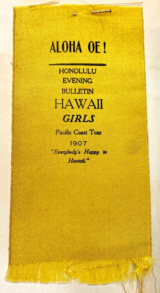 """A close-up color photograph of a flat, yellow ribbon with black text that reads: """"ALOHA OE! HONOLULU EVENING BULLETIN HAWAII GIRLS, Pacific Coast Tour, 1907, 'Everybody's Happy in Hawaii.'"""""""