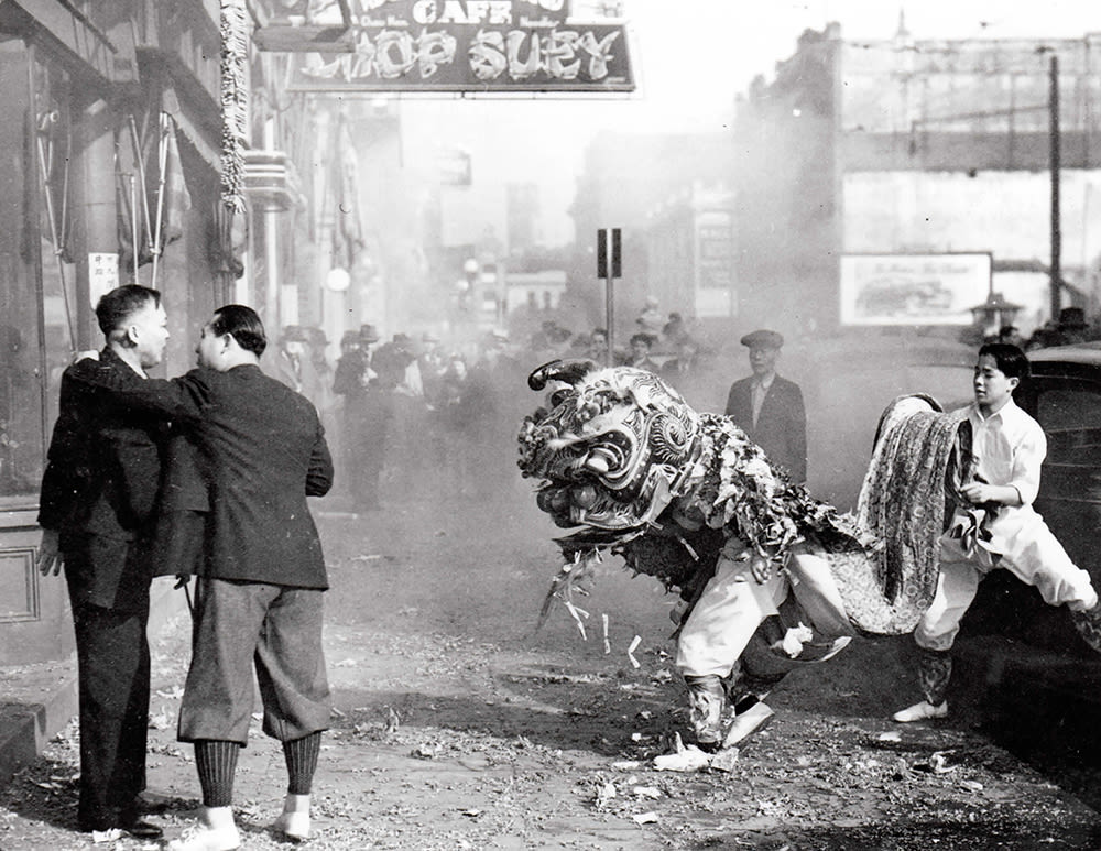 A black and white photograph of an urban sidewalk scene. In the foreground, there are two people in an elaborately designed traditional lion dancer costume. The upper portion of the performer in the front is covered by a large lion headdress. The performer behind holding the tail portion of the lion costume is a young boy. To the left of the performers, two men in suits stand on the sidewalk—one of their arms is around the others'. Behind the performers there is a group of onlookers.
