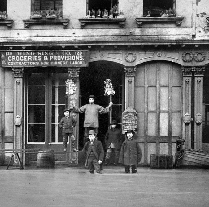 """A black and white photograph of men standing outside Wing Sing & Co. in Portland's Chinatown. The two men in front are knee-deep in floodwater. Two men behind them stand on wood that has been propped up, and one stands on the ground behind them, where water does not appear to have reached. A sign hangs on the building that reads, """"Wing Sing & Co. Groceries & Provisions. Contractors for Chinese Labor."""