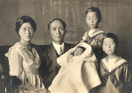 An aged, black and white photograph of a family of five. There is a man wearing a three-piece black suit and black tie holding an infant in a blanket, a woman wearing a white dress and eyeglasses, and two young boys wearing sailor-style shirts.